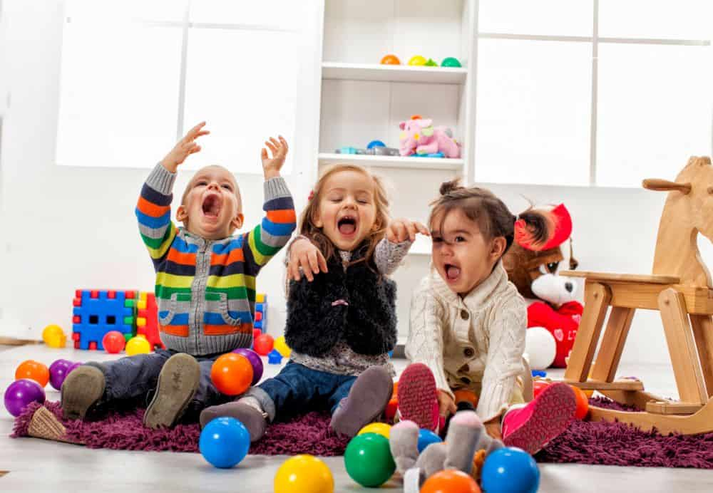 Three little children having fun playing with balls