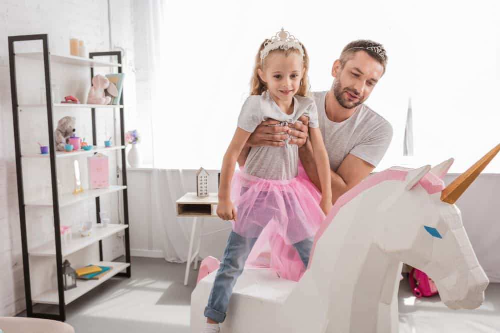 Father putting his daughter on top of a unicorn toy
