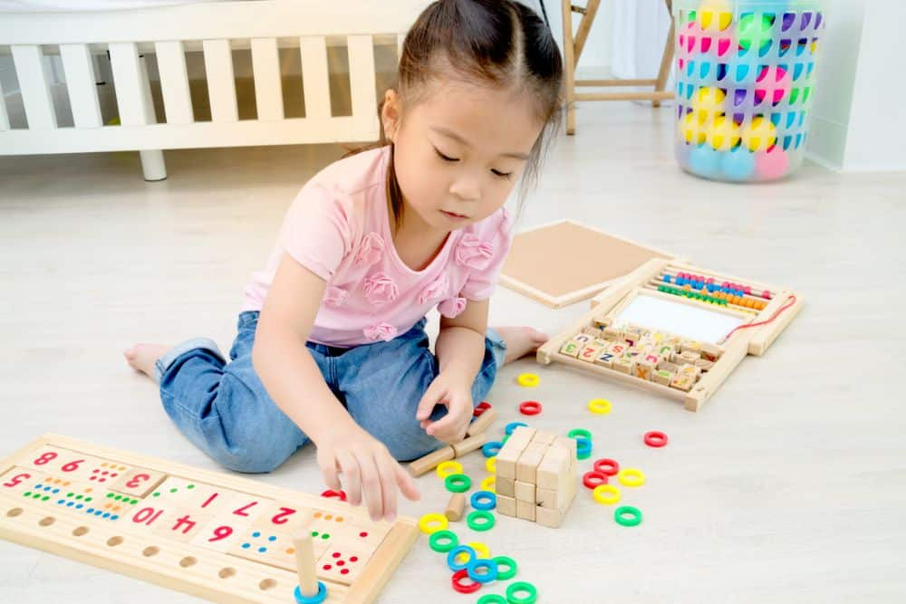 Little asian girl playing with wooden toys