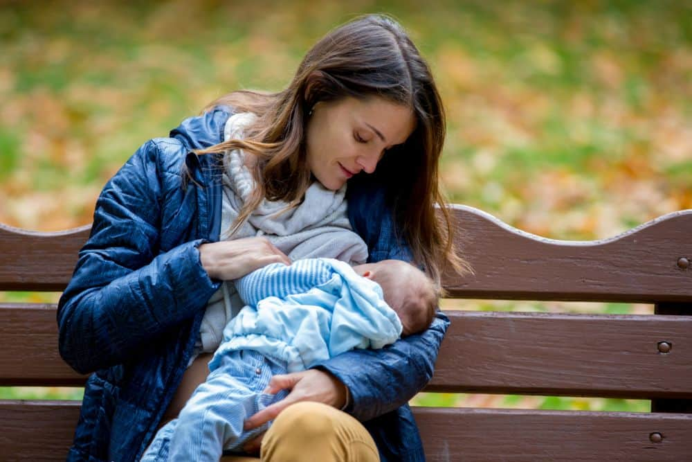 Beautiful mother dressed in warm clothes breastfeeding her baby at the park