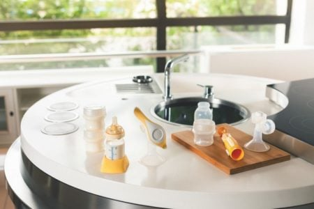 Breast pump and baby bottles laying on the sink counter