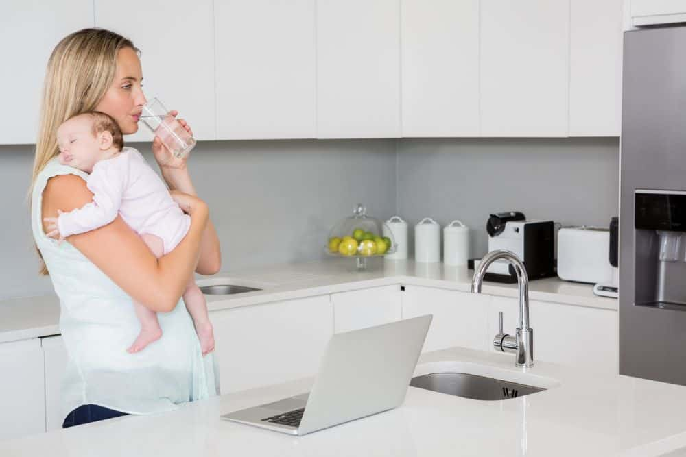 Mom drinking water in kitchen while carrying baby in her arm