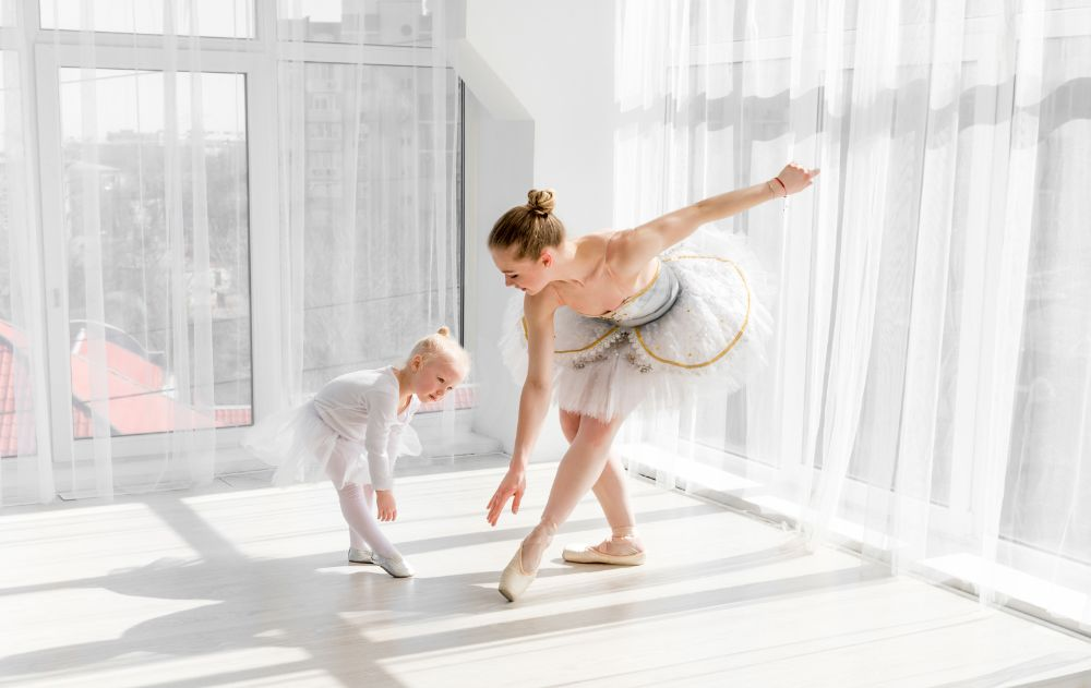 Beautiful ballerina teaching a toddler ballet in a studio