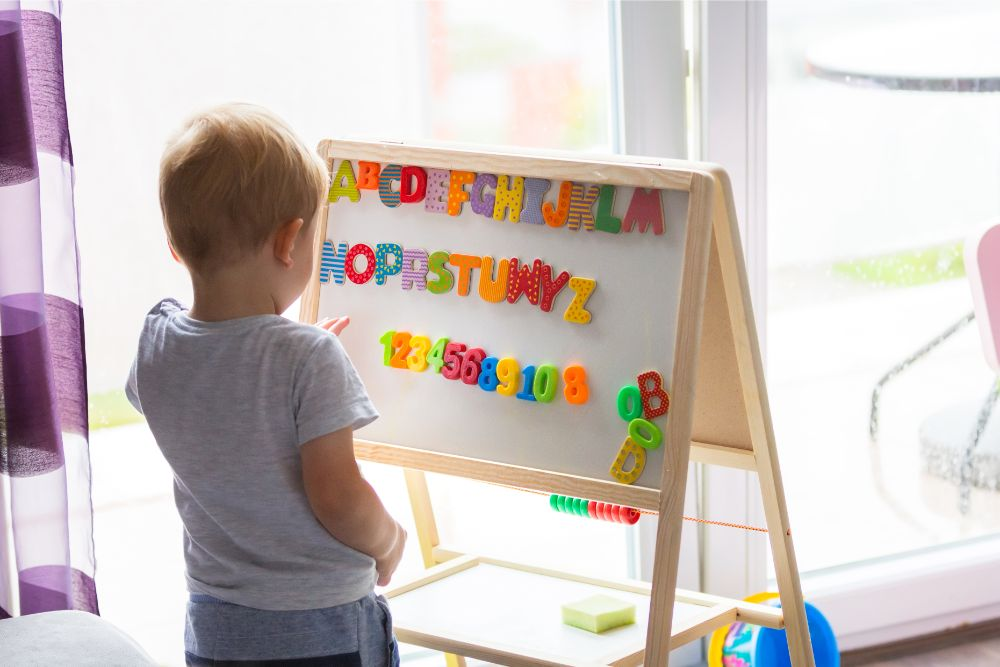 Toddler learning the alphabet on a whiteboard