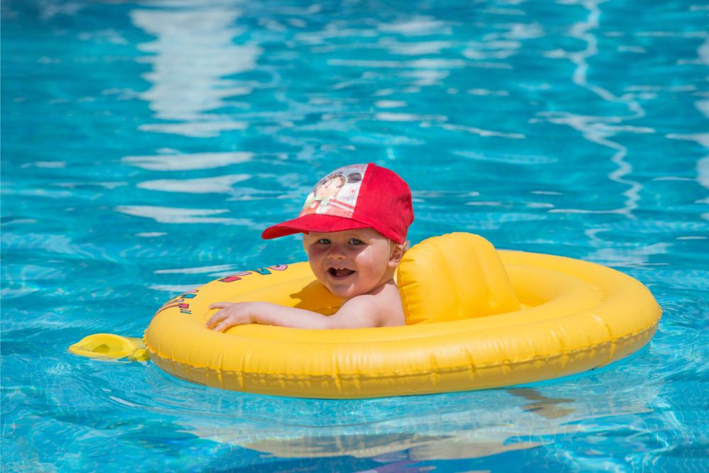 Baby boy in a hat swimming int the pool with a yellow float