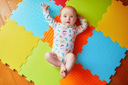 Cute baby lying on a colorful play mat