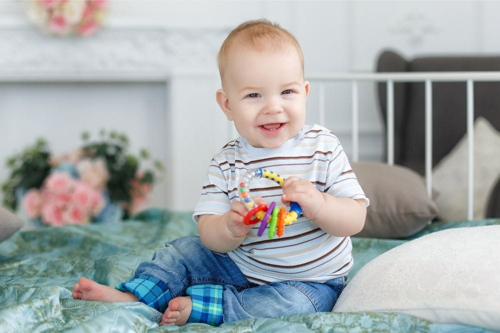 Smiling baby boy in stripes playing with a rattle
