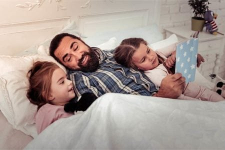 Father reading a book in bed to his two daughters