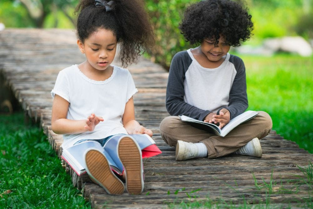 Two young Black kids reading on the ground outside