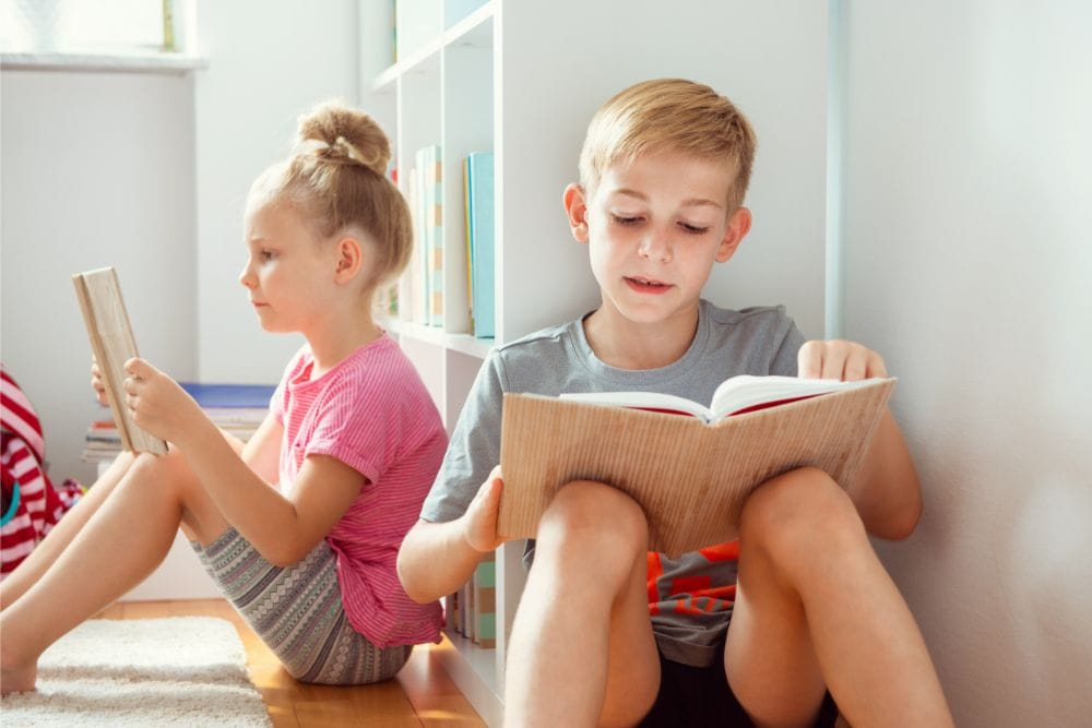 Brother and sister reading on the floor beside a bookshelf