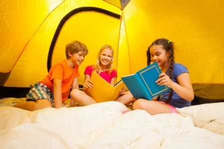 Three preteens reading books inside a tent