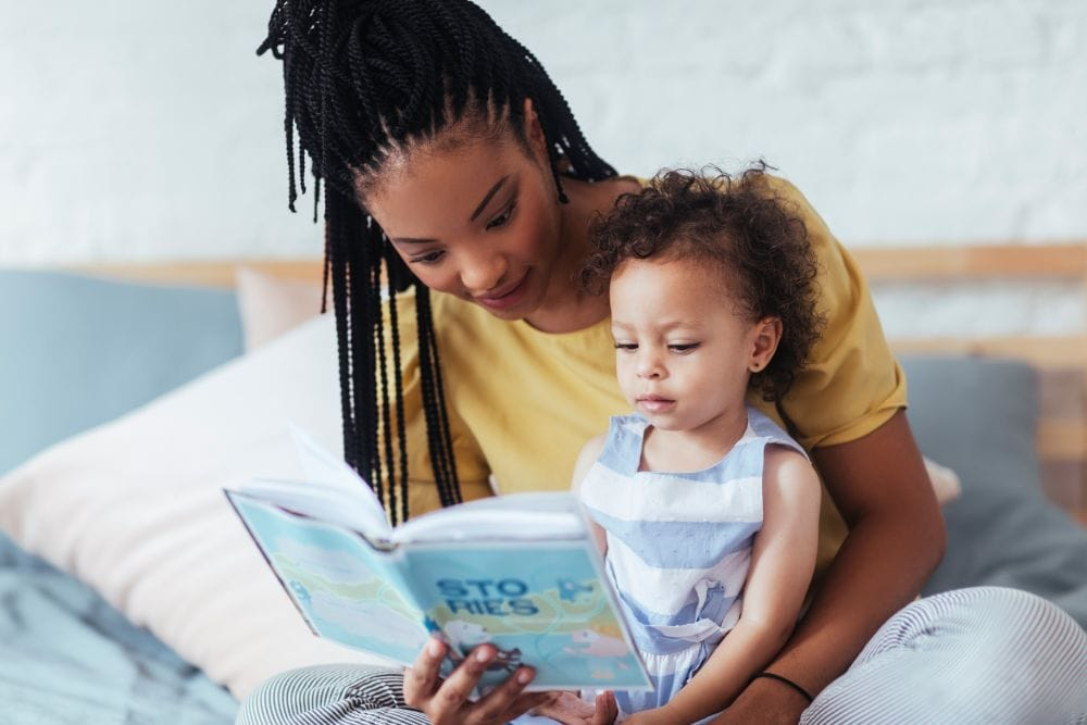 Beautiful African mom reading to toddler