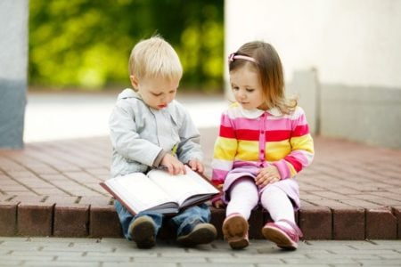 Two cute toddlers reading a book together outdoors