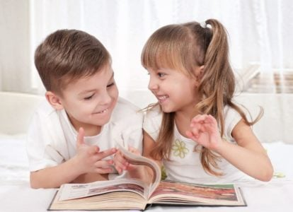Two cute preschoolers in white reading a picture book
