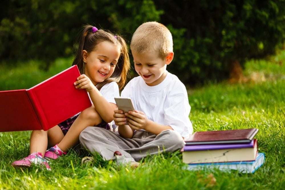 Two adorable preschoolers reading books on the grass