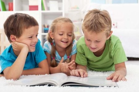 Three cute laughing kids reading a book on the floor