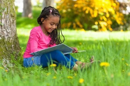 Beautiful Black girl sitting underneath a tree while reading a book