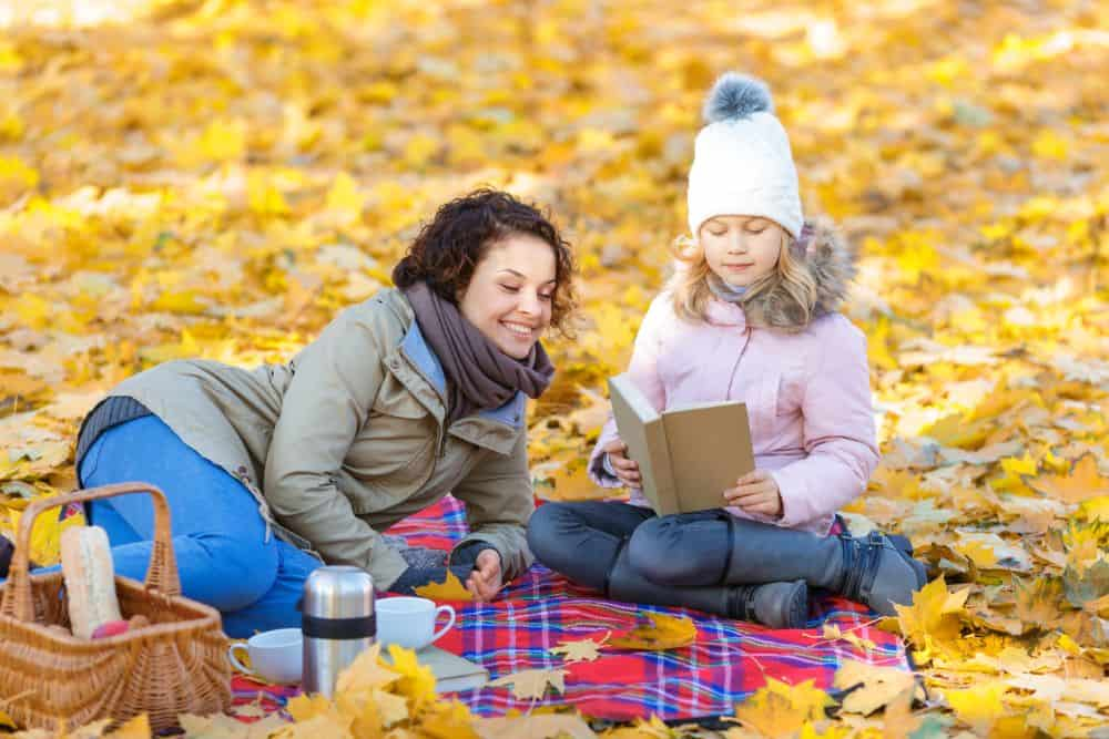 Mother and daughter reading at the park