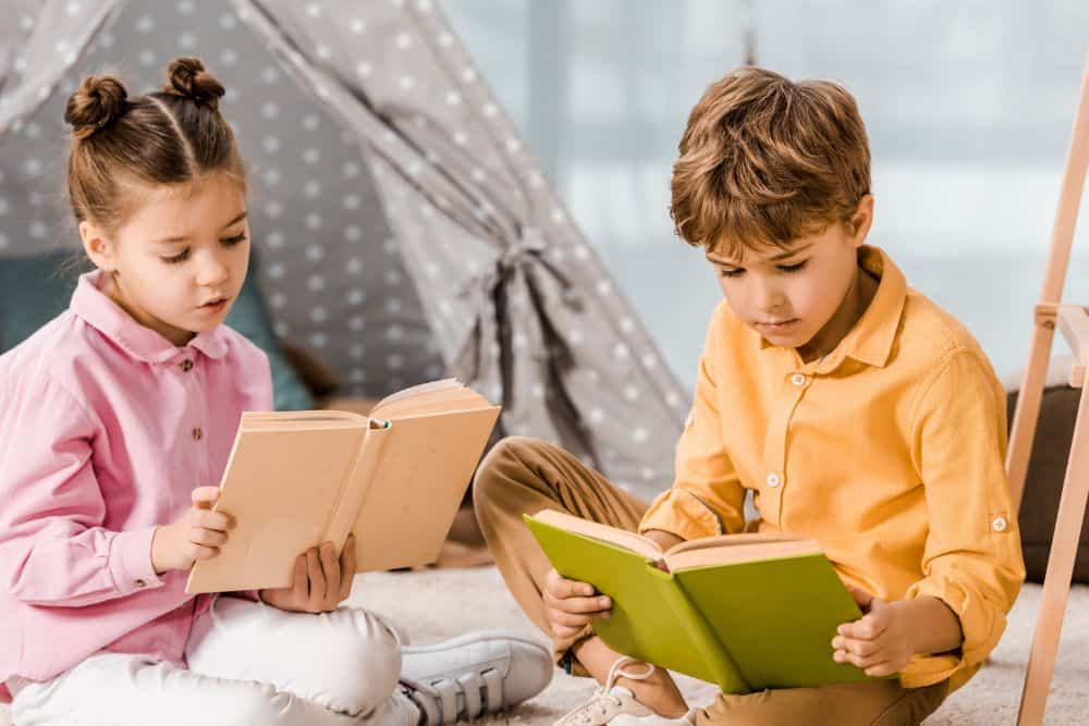 Young brother and sister reading books