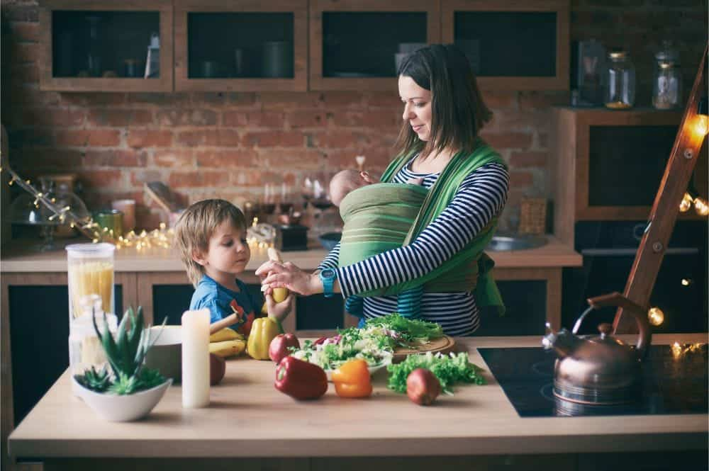 Mother preparing food in the kitchen with baby and young son