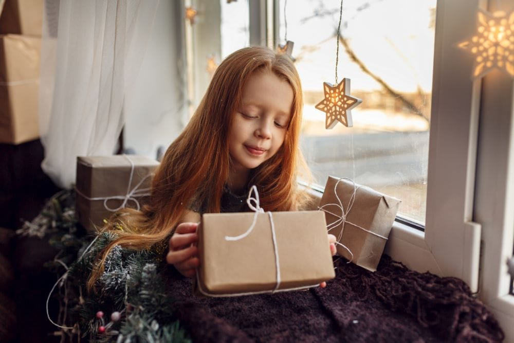 Beautiful young girl opening a gift by the window