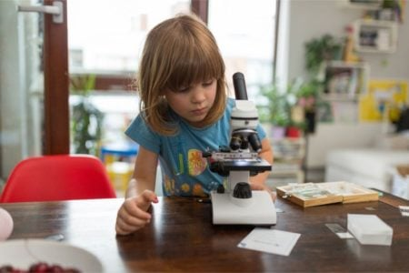 Young kid playing with microscope