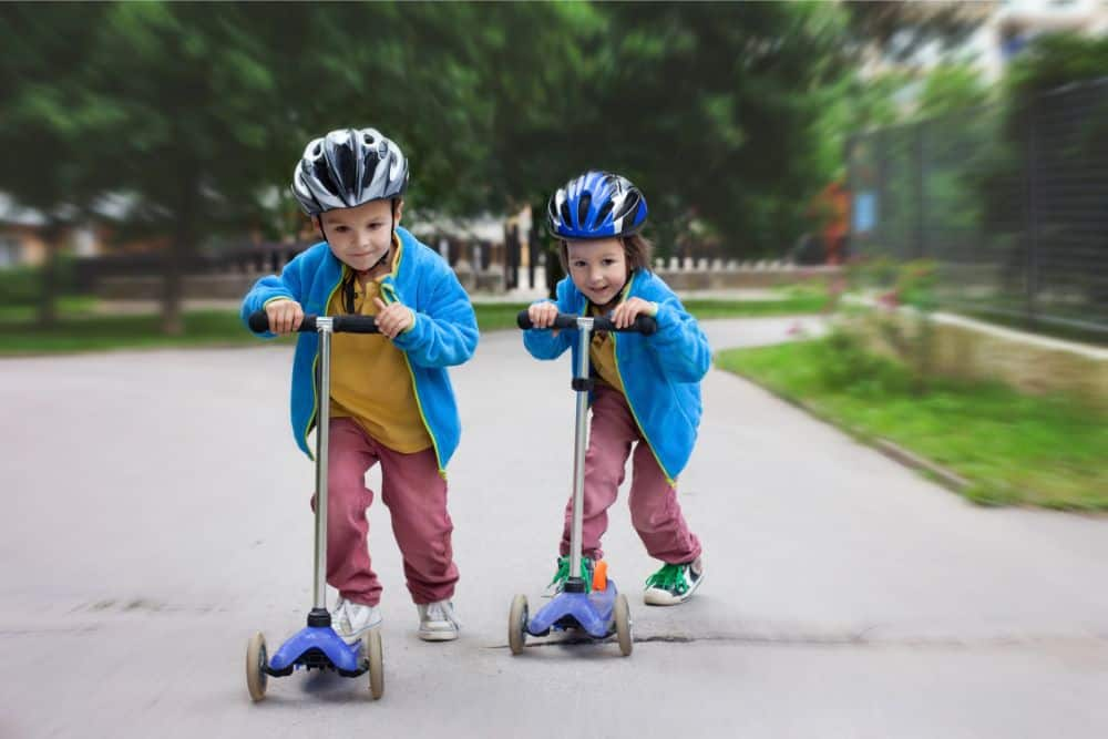 Two little boys racing with their scooters