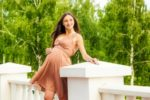 Beautiful confident pregnant woman in a dress posing on the porch