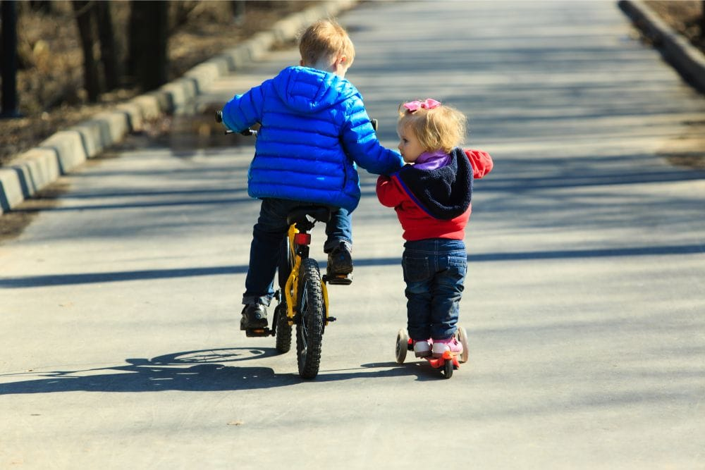 Little boy riding a bike and teaching toddler sister to ride a scooter