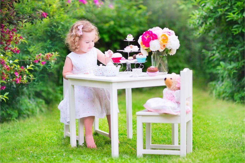 Beautiful little girl having tea party outside with her teddy