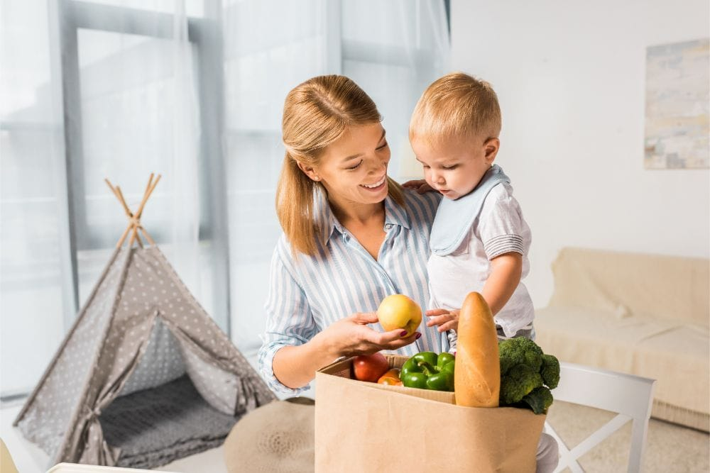 Smiling mother showing the groceries to her baby while carrying him