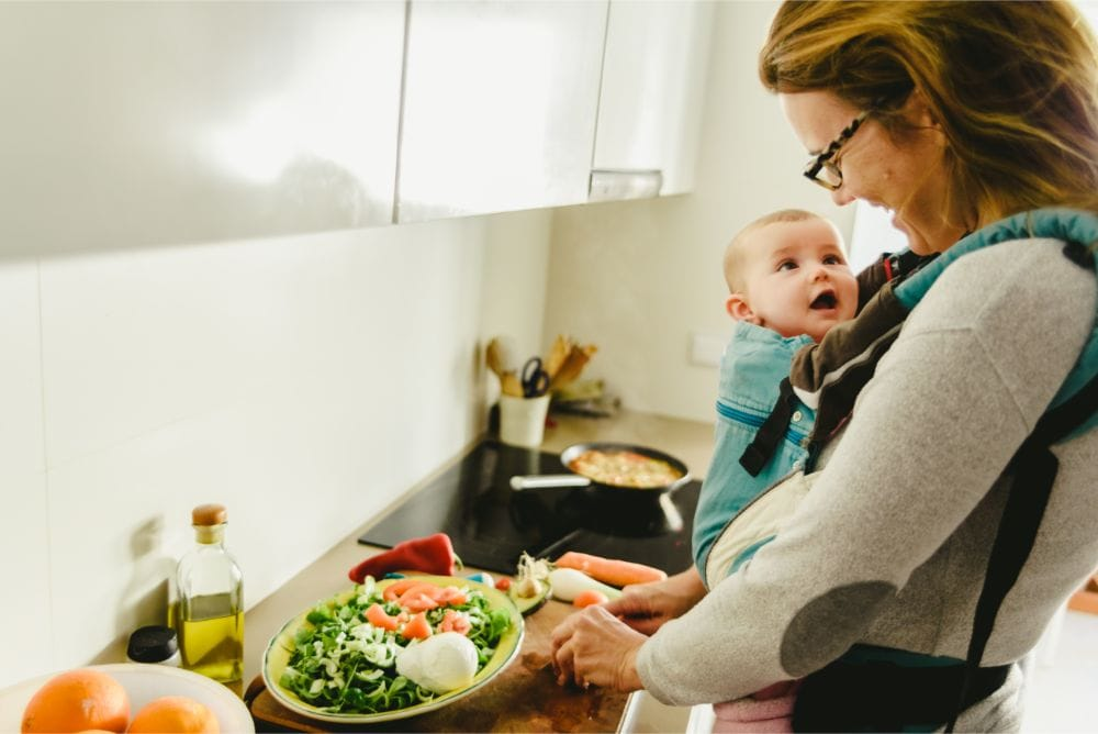 Mother smiling at her baby in carrier while making breakfast