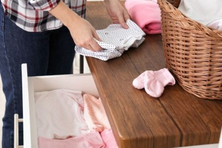 folding baby clothes on top of drawer