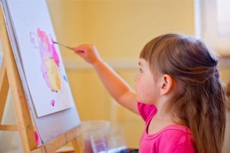 Cute little girl painting on an easel