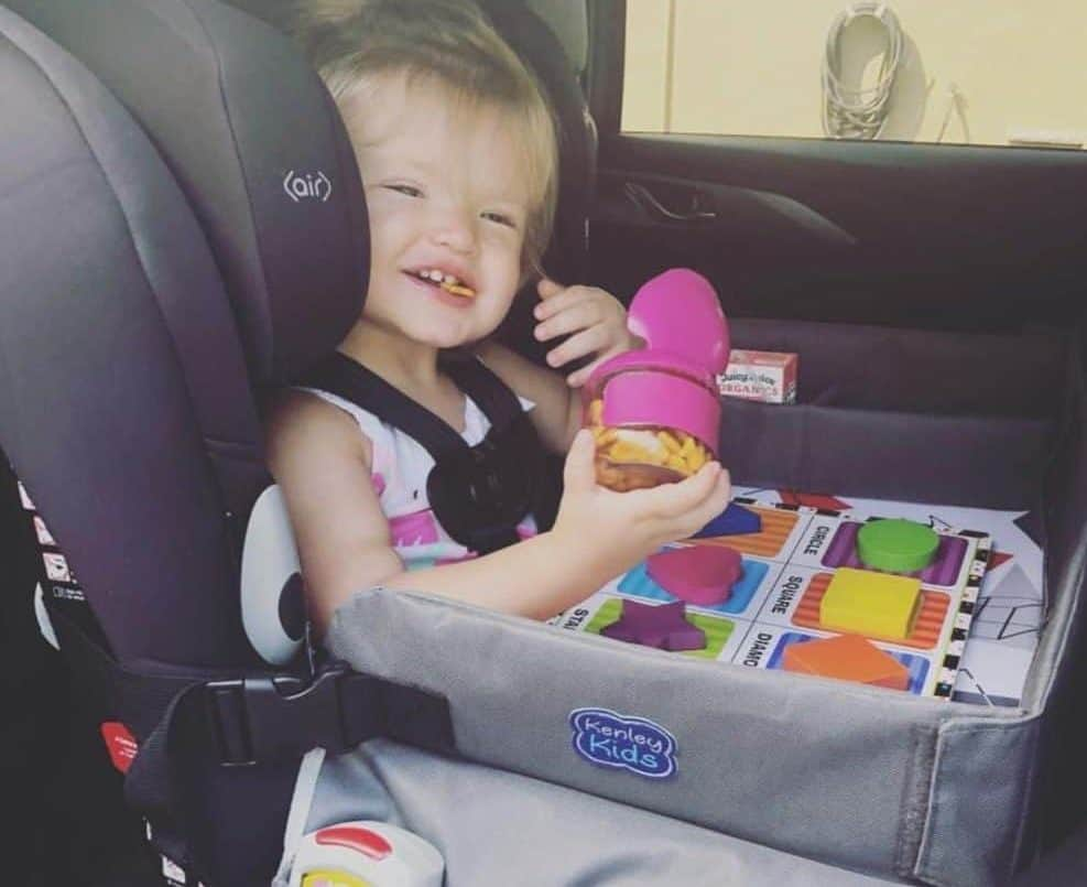 Smiling toddler playing with a travel tray in her car seat