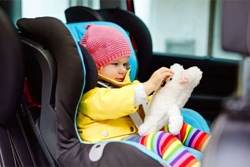 Toddler playing with teddy bear in her car seat
