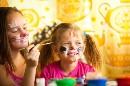 Two sisters painting their faces