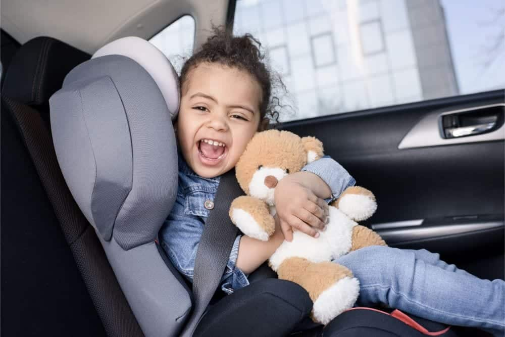 Happy little girl holding her teddy bear in a child car seat
