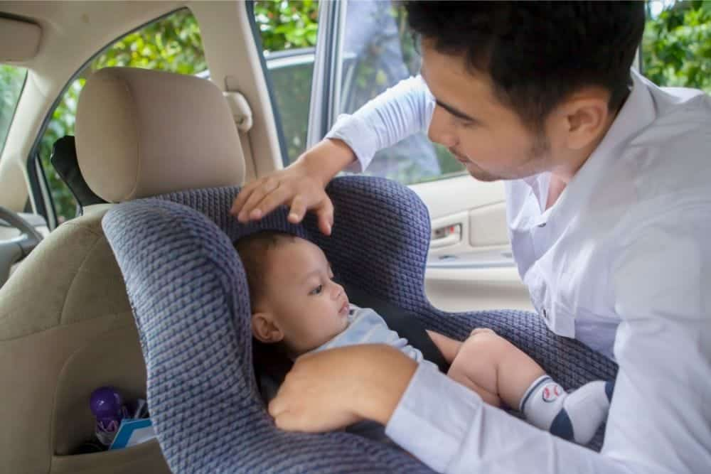Father putting his baby in a rear facing car seat