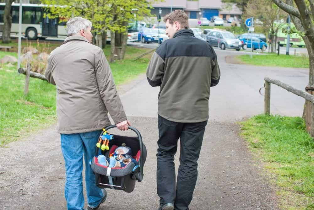Grandfather carrying his grandson in a car seat while walking with his son