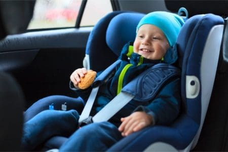 Smiling toddler in a car seat eating a cookie