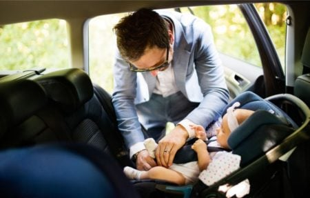 Dressed up father securing his baby's seatbelt in the car seat