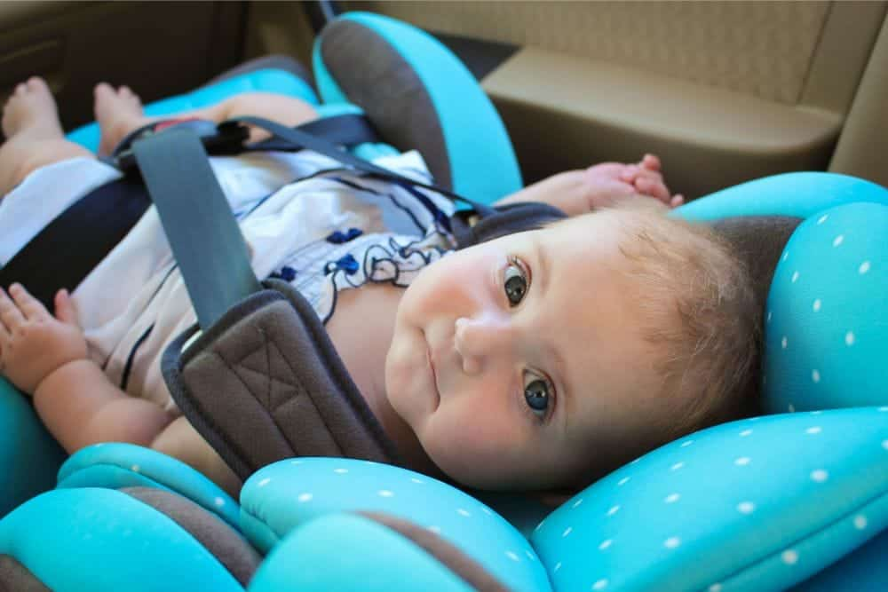 Adorable infant looking up from her blue car seat