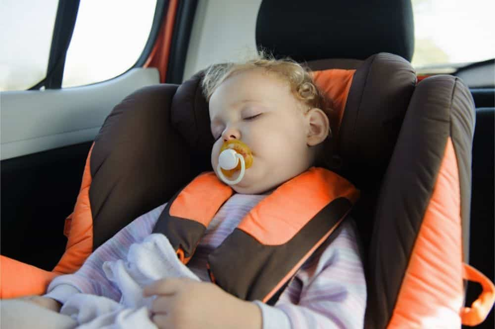 Baby girl sucking on a pacifier while sleeping in a car seat