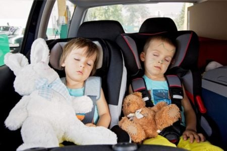 Two little boys sleeping in their car seats with stuffed toys