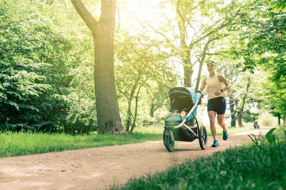 Mom jogging at the park with baby in a stroller