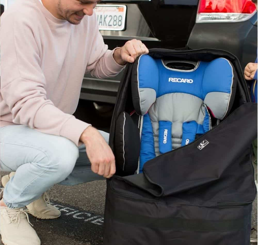 Dad taking out a car seat from its travel bag
