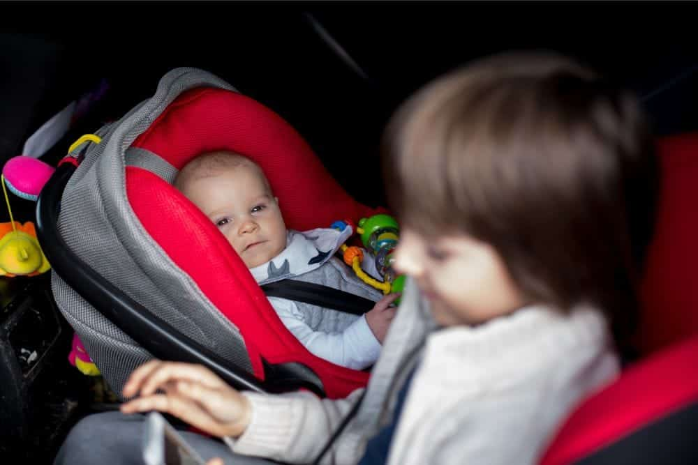 Infant in rear facing car seat watching his brother