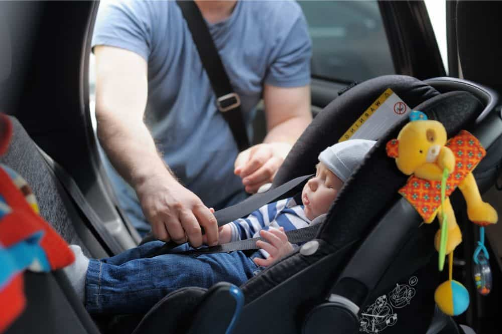 Dad fastening baby in a car seat of a small car