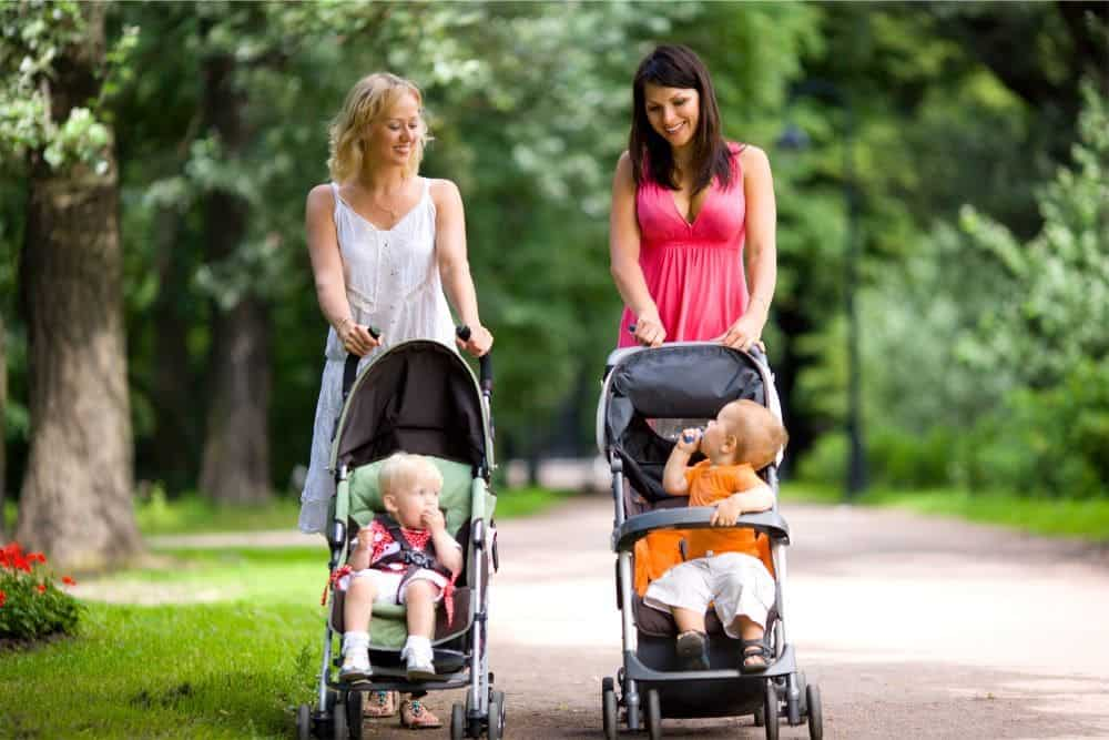 Two moms walking their babies in strollers at the park